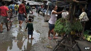 A child walks in a mud puddle at Dili's traditional market on March 15, 2012