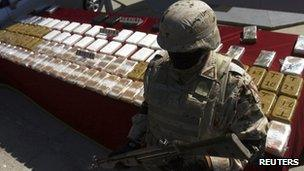 A soldier stands next to packages containing confiscated drugs during a presentation to the media in Tijuana, 14 March 2012
