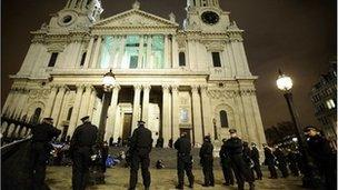 Riot police stand guard as they prepare to remove protesters from the Occupy encampment in front of St Paul's Cathedral