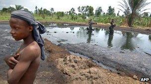 Boy stands near an abandoned oil well head leaking crude oil, 11 April 2007, in Kegbara Dere, Ogoni Territory