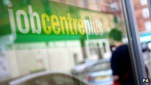 A man looks in the window of a job centre