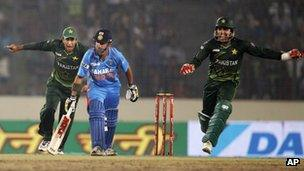 Pakistan's Umar Akmal, right, and Nasir Jamshed, left, celebrate the dismissal of India's Gautam Gambhir, center, during their Asia Cup cricket match in Dhaka, Bangladesh, Sunday, March 18, 2012.