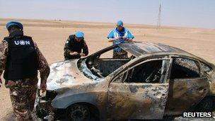 UN observers by a burnt-out car in Syria