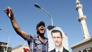 A pro-Assad demonstrator shouts slogans in Damascus while holding up a picture of Bashar al-Assad.