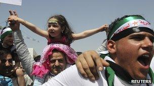 A girl with a Syrian opposition flag painted on her forehead, sits on a man's shoulders during a demonstration by Syrian refugees against President Bashar Al-Assad outside the Syrian embassy Jordan.