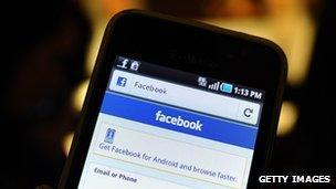 A smartphone displays a Facebook app