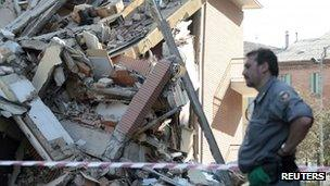 A rescue worker stands in front of a damaged building in Cavezzo