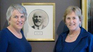 Craigie and Debbie Zildjian stand in front of a photograph of Avedis Zildjian
