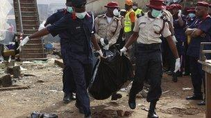 Rescue workers carry bodies at the site of a plane crash in Lagos, Nigeria, Monday, 4 June 2012