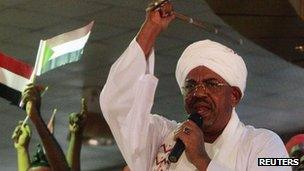 Supporters wave Sudanese flags as Sudan's President Omar al-Bashir addresses supporters during a rally at the ruling party headquarters in Khartoum, 18 April 2012