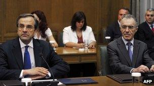 Greece's new Prime Minister Antonis Samaras (L), Finance Minister Vassilis Rapanos attend the first cabinet meeting at the Greek Parliament in Athens on June 21, 2012.