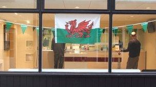 Fflag Cymru a fflagiau gwyrdd yr Eisteddfod mewn ffenestr siop