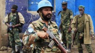 A UN peacekeeper walks past rebel soldiers in Bunagana, on the DRC border with Uganda