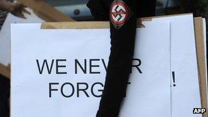 Woman wearing anti-Nazi badge and carrying banner in Budapest, (16 July 2012)