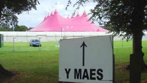 Arwydd 'Y Maes' o flaen y Pafiliwn pinc
