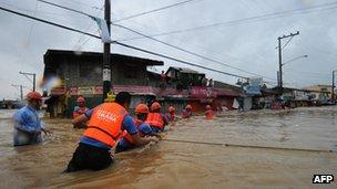 Rescuers crossing flood waters to help evacuate residents from their homes