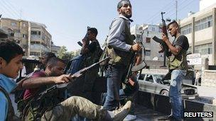 Free Syrian Army members are pictured on a truck as they prepare to move into a district of Aleppo
