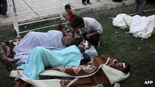 Injured Iranians lie on the grass outside a hospital in the town of Ahar