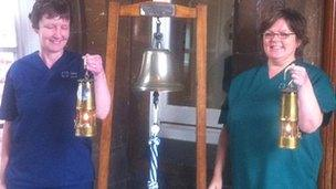 Sister Margo Lord [L] and Miriam Jenkins with the flame at Rookwood Hospital, Llandaff