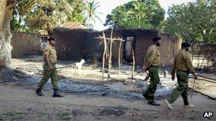 Police walk past the remains of houses which were burned down during clashes in Chamwanamuma village, Tana River delta, north of Mombasa in Kenya Friday, Sept. 7, 2012.