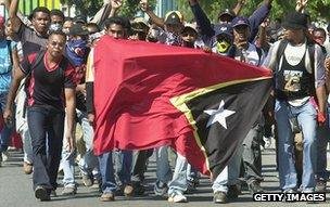 Men carry East Timor flag through Dili, 19 May 2002