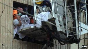 Pakistani rescuers remove a body from the garment factory