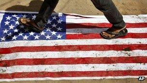 An Indian man walks over an American flag during a protest against the Innocence of Muslims film mocking the Prophet Muhammad in Hyderabad, India, on Friday