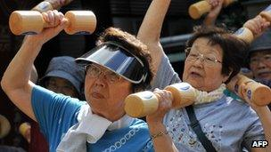 Elderly people work out with wooden dumb-bells in Tokyo, Japan