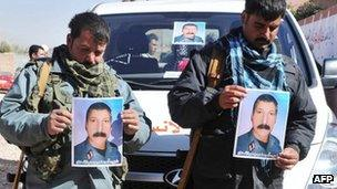 Afghan police officers hold a picture of their commander, killed during combat with Taliban forces in Herat's Obe district.