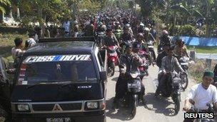 Residents carrying wooden sticks on motorcycles during clashes in Lampung, 29 October 2012