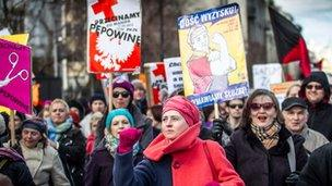 """Polish feminists hold placards reading """"Cut the Cord"""" (between the State and the Church) and """"Enough exploitation, we quit!"""" March 2012"""