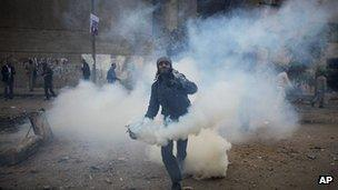 A protester throws a tear gas canister away near the interior ministry during clashes with the Egyptian riot police, not seen, in downtown Cairo, Egypt, Sunday, Nov. 20, 2011