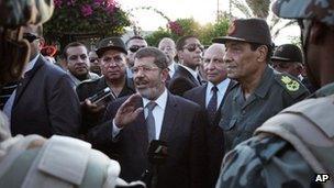 In this Sunday, 6 Aug 2012 image, Egyptian President Mohammed Mursi, centre, and Field Marshal Gen Hussein Tantawi, right, visit soldiers in Egypt's northern Sinai Peninsula
