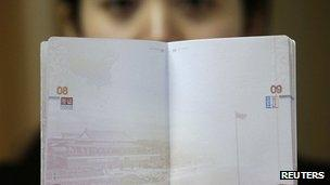 A woman holding up the new Chinese passport with a controversial map