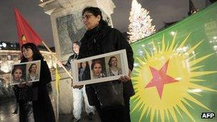 A woman of Kurdish origin holds a frame with photos of three Kurdish women activists