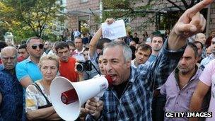 A man shouts during a protest rally against torture in prisons as demonstrators block one of the capital's main streets in Tbilisi on September 19, 2012.