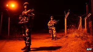 Indian Border Security Force (BSF) soldiers patrol along the border fence at an outpost along the India-Pakistan border in Abdulian, 38 kms southwest of Jammu, on January 17, 2013.