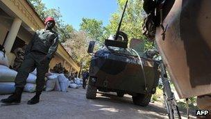 A Malian soldier walks past French military vehicles in the city of Niono