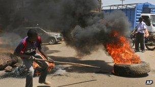 A protester next to a burning barricade in Kisumu, Kenya on 20 January 2013