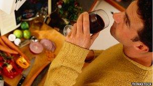 Man drinks wine while cooking