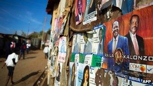 People walk past campaign posters in Nairobi's Kibera slum on 27 February 2013