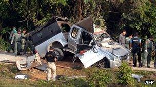 Thai bomb squad members inspect the site of a roadside bomb attack by suspected separatist militants in Thailand's restive southern province of Narathiwat, 30 January 2013