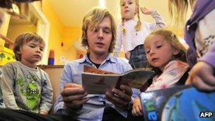 A teacher at a German kindergarten reads a story