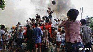 Ethnic Rakhine people get water from a fire truck to extinguish fires during fighting between Buddhist Rakhine and Muslim Rohingya communities in Sittwe, 10 June 2012