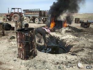 A Syrian man in the Raqqa countryside pours crude oil brought from Deir al-Zour province into a pit where it will be distilled as part of the refining process to produce fuel (15 April 2013)