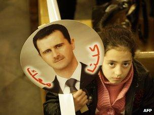 """A Syrian girl carries a picture of Bashar al-Assad saying """"we are with you"""" during a Mass at a Greek Orthodox church in Damascus (9 January 2012)"""