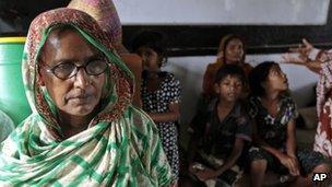 Bangladeshis rest at a cyclone shelter, 16 May 2013