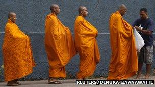 A devotee offers alms to Buddhist monks walking down a road to mark Vesak day in Colombo (25 May 2013)