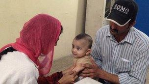 Family getting a measles vaccination for their child at a hospital in Lahore