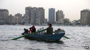 An Egyptian woman rows a boat with her family along the Nile River, in Cairo